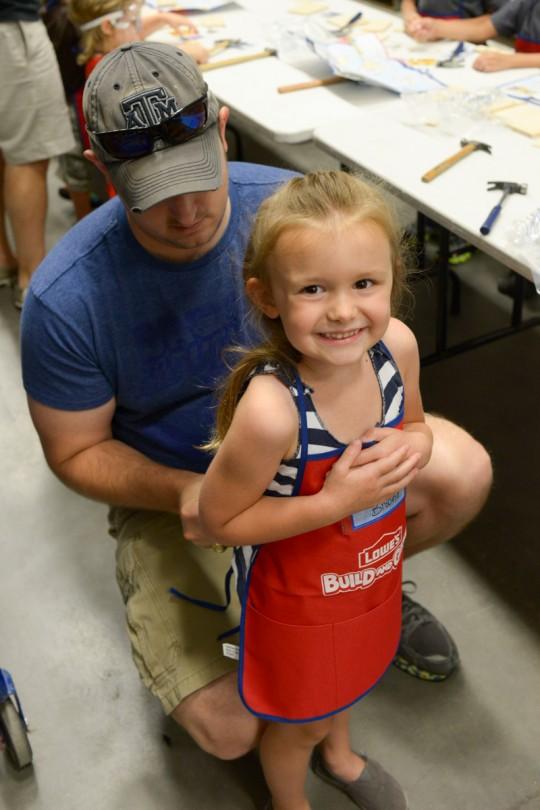 Daddy putting on her work vest.